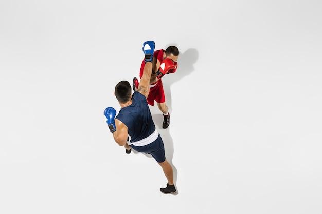 Boxe de dois boxeadores profissionais isolado no fundo branco do estúdio, ação, vista superior. alguns atletas caucasianos musculosos em forma lutando. conceito de esporte, competição, emoção e emoções humanas.