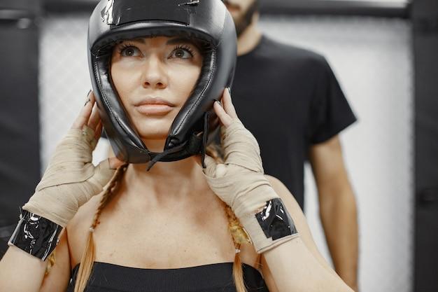 Boxe de mulher. iniciante em uma academia. senhora em uma roupa esporte preta. mulher com o treinador.