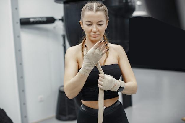Boxe de mulher. iniciante em uma academia. senhora em uma roupa esporte preta.