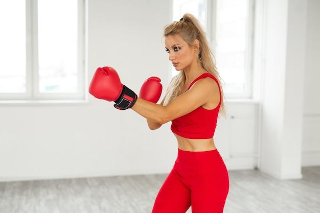 Boxe treinamento linda mulher em um terno esportivo vermelho