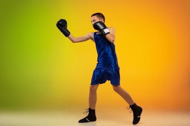 Boxeador adolescente contra fundo de estúdio de néon gradiente em movimento de chute, boxe
