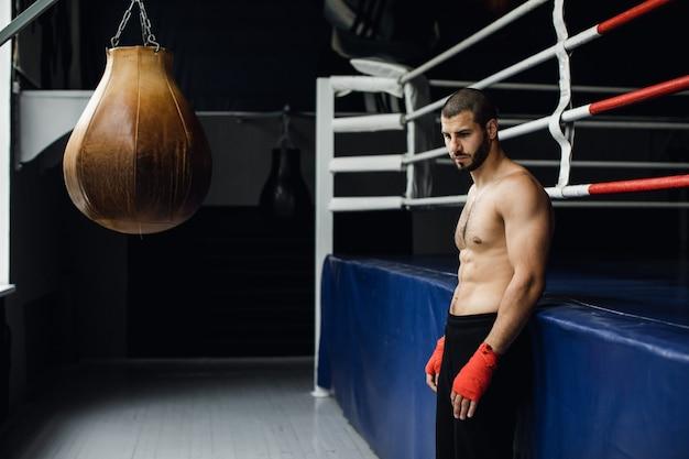 Boxeador de peito nu fica perto do ringue. foto de alta qualidade