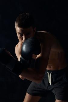 Boxeador em luvas em um fundo preto curvado cortado