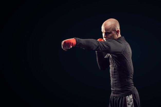 Boxeador esportista lutando no espaço negro, conceito do esporte de boxe