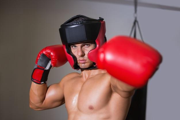 Boxeador masculino atacando com a esquerda no clube de saúde
