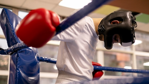 Boxeador masculino com capacete e luvas no ringue praticando