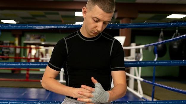 Boxeador masculino próximo ao ringue envolvendo as mãos com proteção
