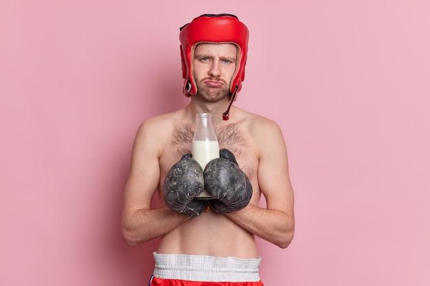 Boxeador masculino sem camisa tem expressão facial descontente segura garrafa de leite usa luvas esportivas se sente cansado após o treino.