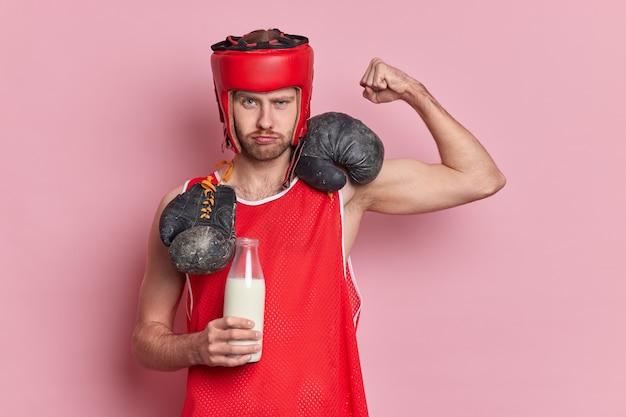 Boxeador masculino sério levanta o braço mostra bíceps bebe leite fresco para ser forte usa chapéu de proteção, camiseta vermelha, luvas de boxe em volta do pescoço demonstra poder