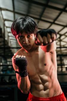 Boxeador musculoso usando pulseira preta no pulso e faz o soco de aquecimento