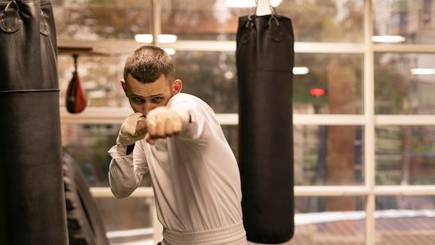 Boxeador praticando com sacos de boxe