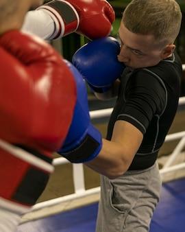 Boxeador praticando no ringue com treinador