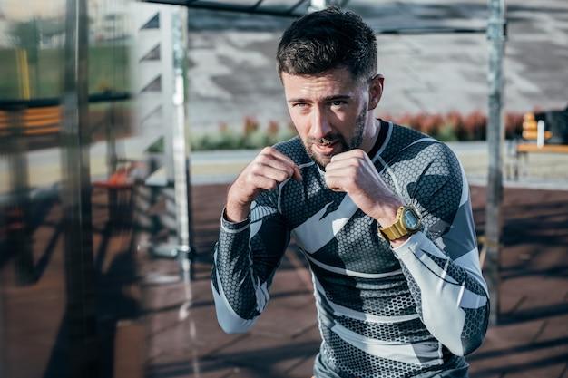 Boxeador sério e concentrado dominando seus golpes ao ar livre enquanto treinava sozinho no campo de esportes