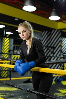Boxeadora com corpo musculoso em pé dentro de um ringue de boxe