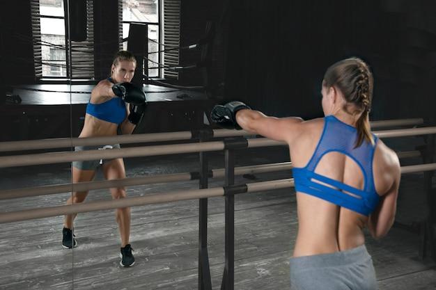 Boxeadora praticando socos em frente ao espelho