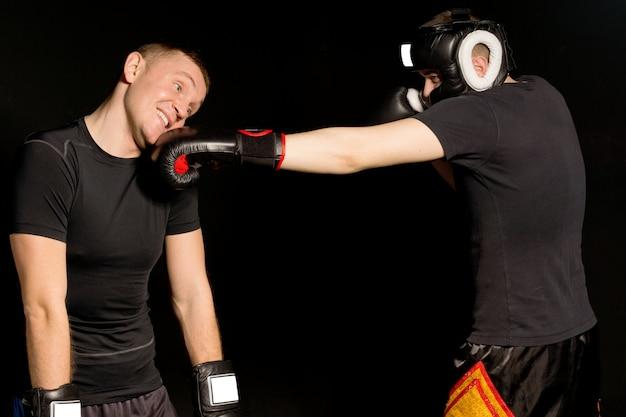 Boxer acertando um soco na mandíbula de seu oponente enquanto os dois lutam no ringue