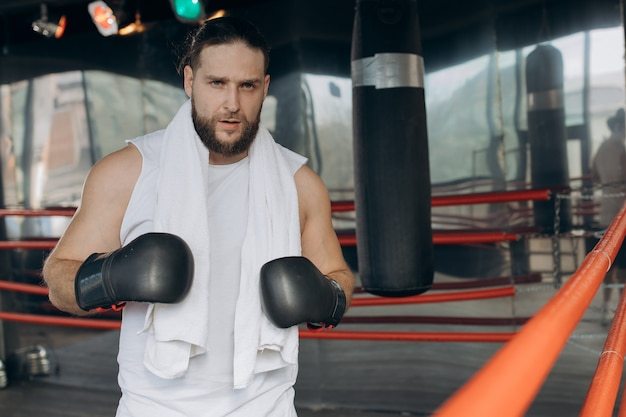 Boxer após o treino no ringue. retrato de boxeador esportivo suado usando bandagens de boxe