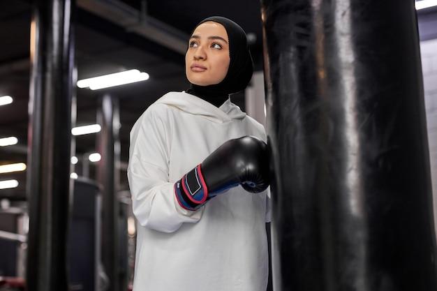 Boxer árabe feminina posando no ginásio, jovem treina com pesado saco de pancadas. retrato de mulher confiante em uma saída de trabalho, fazendo uma pausa e olhando para o lado, em hijab esportivo branco