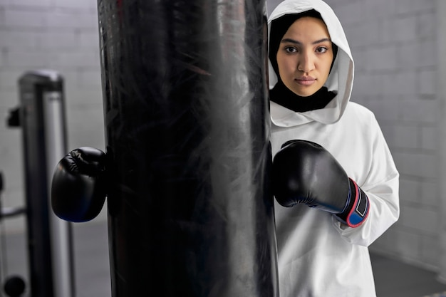 Boxer árabe feminina posando no ginásio, jovem treina com pesado saco de pancadas. retrato de mulher confiante em uma saída de trabalho, fazendo uma pausa, em hijab esportivo branco