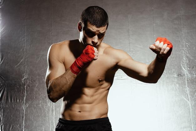 Boxer atlético socando com determinação e precaução sobre kground prata