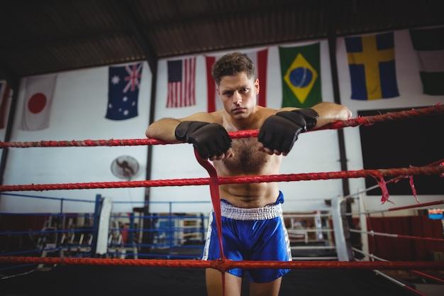 Boxer cansado, apoiando-se no ringue de boxe