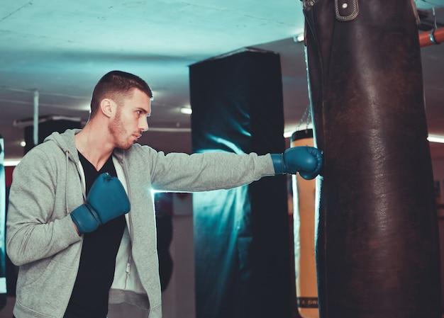 Boxer concentrado golpe direto com saco de pancadas