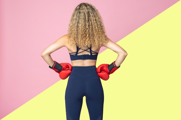 Boxer de mulher bonita de cabelos loiro e vestido com roupas esportivas está sorrindo alegremente em um isolado de duas cores rosa e amarelas