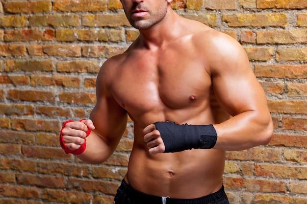 Boxer de músculo em forma de homem com bandagem de punho