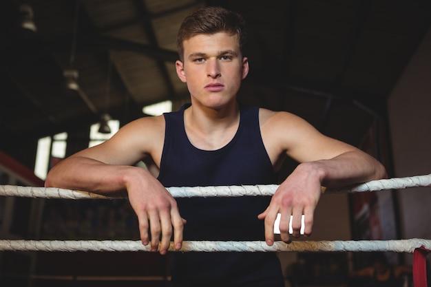 Boxer em pé no ringue de boxe