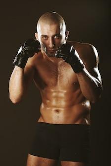 Boxer em um rack com um belo corpo musculoso e careca