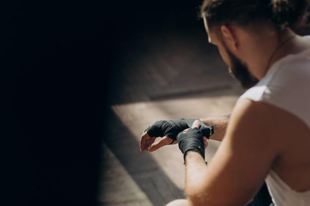 Boxer envolve as mãos. boxer de homem embrulhando as mãos se preparando para uma luta
