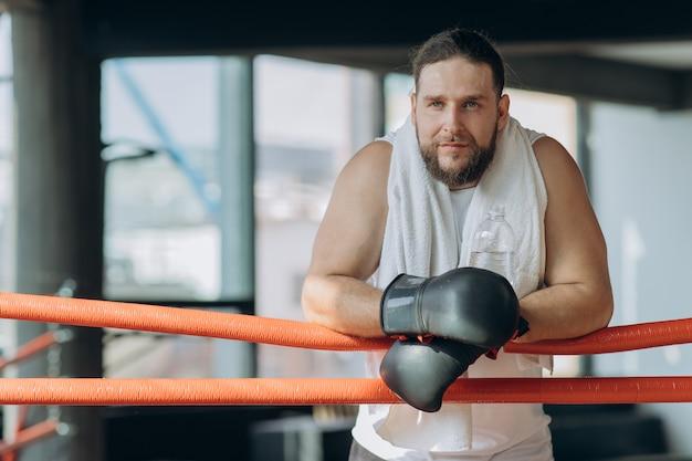 Boxer esportivo suado usando ataduras de boxe nas mãos, olhando na câmera do anel enquanto descansa após treino no ginásio