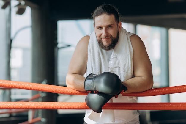 Boxer, fazer uma pausa para beber da garrafa de água após o treino no ginásio.