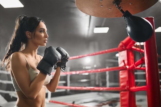 Boxer fêmea batendo pequeno saco de pancadas.