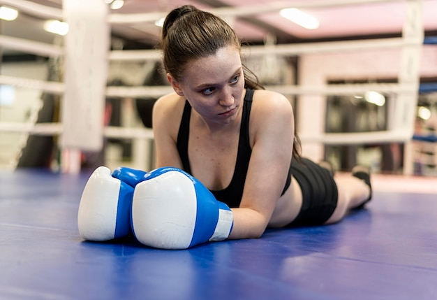 Boxer fêmea com luvas de proteção no chão