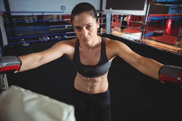 Boxer fêmea confiante em pé no ringue de boxe