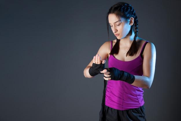 Boxer fêmea está envolvendo as mãos com envoltórios de boxe pretos