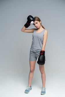 Boxer feminina com luvas de boxe em pé na cinza olhando para baixo