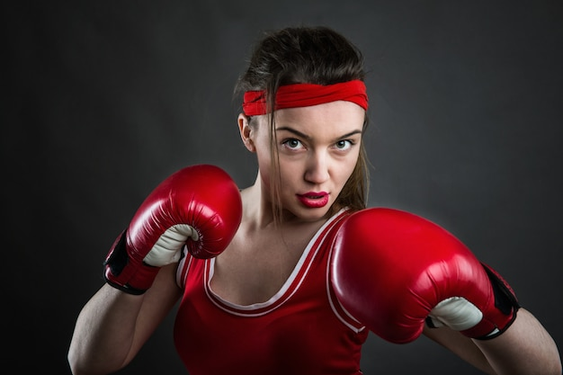 Boxer feminina em luvas de boxe vermelhas e roupas esportivas, vista frontal. conceito de esporte de luta