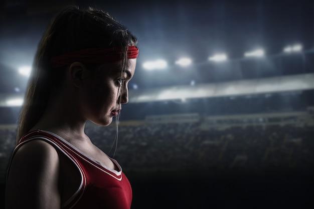 Boxer feminina em sportswear vermelho antes da luta, vista lateral. mulher no ringue de boxe