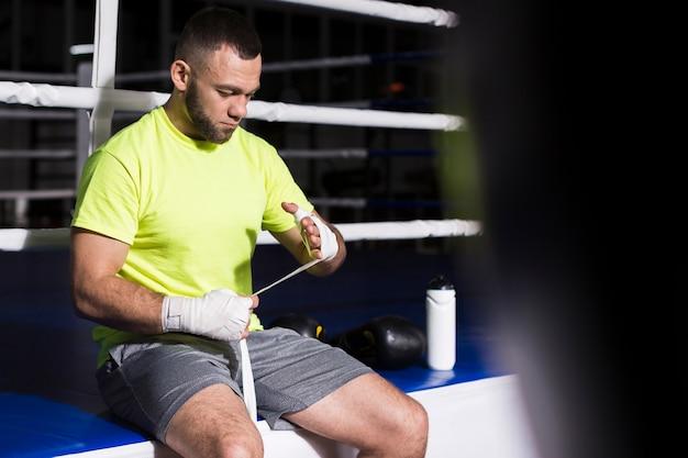 Boxer masculino ao lado do anel, colocando a proteção para as mãos