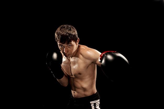 Boxer masculino boxe em saco de pancadas com iluminação nervosa dramática em preto