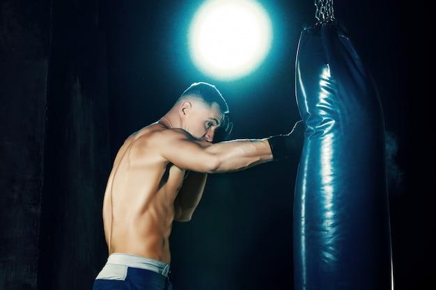 Boxer masculino boxe em saco de pancadas com iluminação nervosa dramática