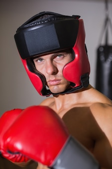 Boxer masculino em posição defensiva no health club