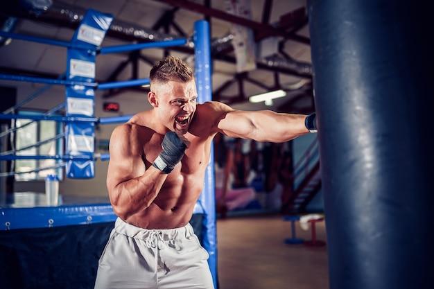 Boxer masculino treinando com saco de pancadas no pavilhão desportivo escuro.