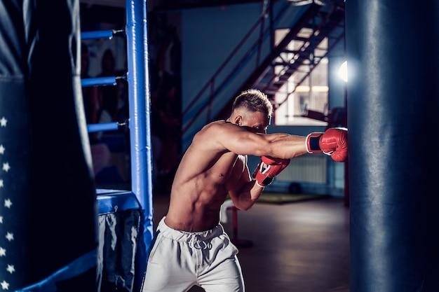 Boxer masculino treinando com saco de pancadas no salão de esportes escuro.