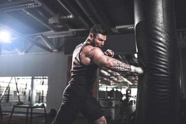 Boxer masculino treinando com saco de pancadas no salão de esportes escuro