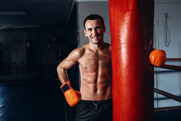 Boxer masculino treinando no ginásio escuro.