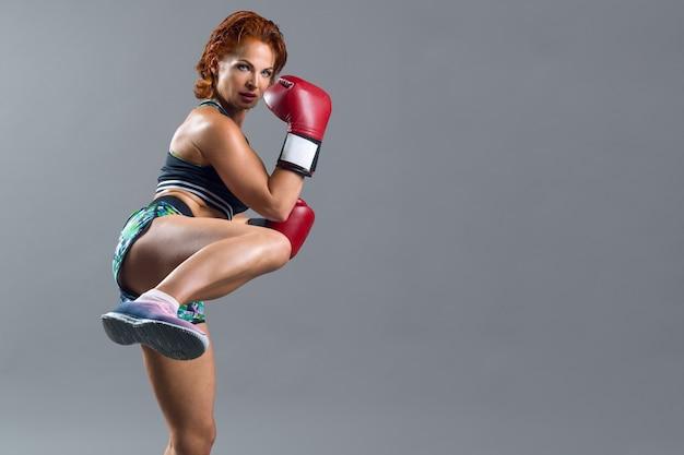 Boxer mulher madura atlético com luvas vermelhas em roupas esportivas