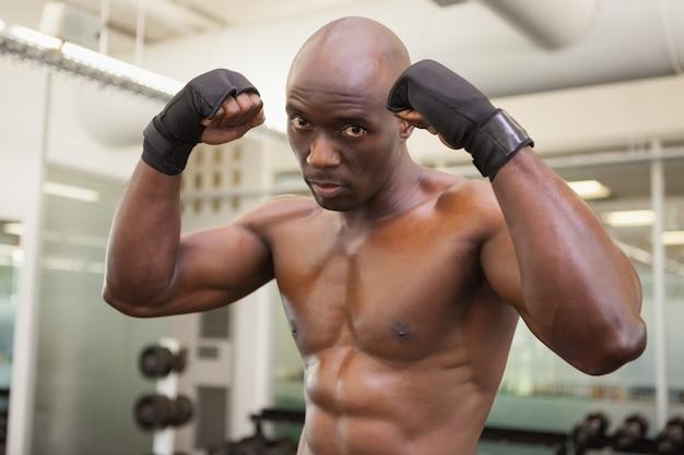 Boxer muscular em posição defensiva no health club